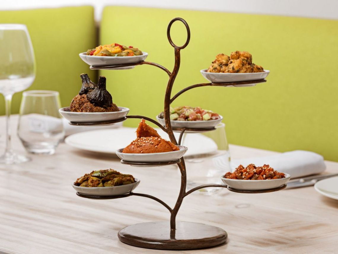 A decorative metal tree-like sculpture with dishes sitting on its branches sits on a table with place settings