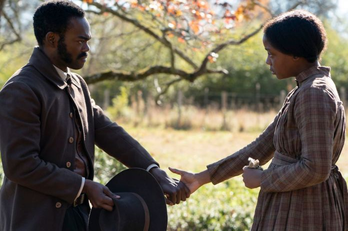 A Black man and woman in Antebellum dress stand distanced from each other, reaching across the gulf between them to touch hands in Barry Jenkins' The Underground Railroad