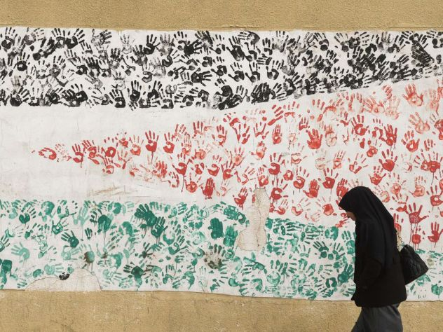 A woman passes in front of the graffiti that depicts a Palestinian flag in the city center of Amman on February 12, 2019.
