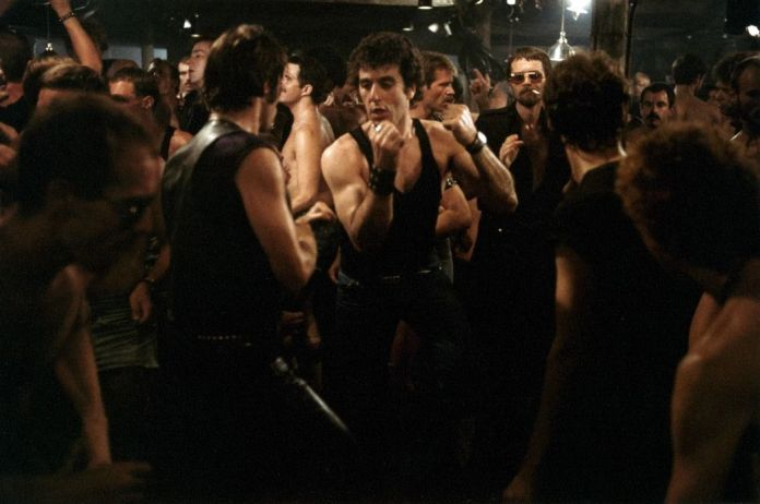 Al Pacino, in jeans and a black sleeveless T-shirt, dances in a crowd of men at a gay bar in Cruising.