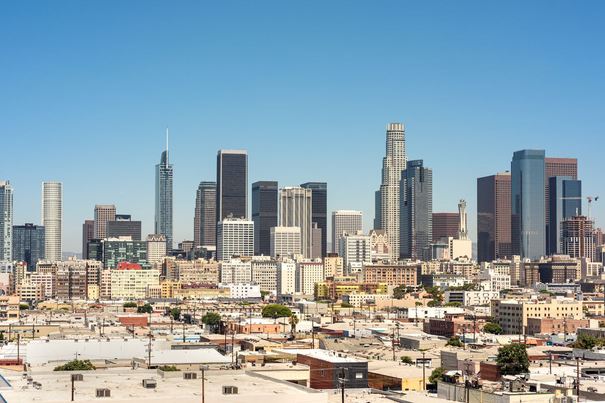 The Los Angeles skyline against a blue sky.