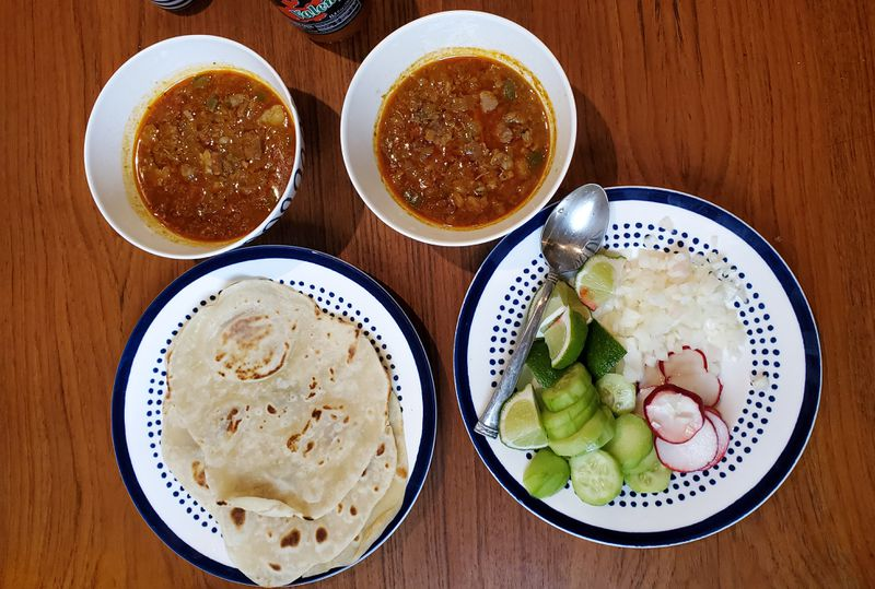 two bowls of salsa beside a plate of flour tortillas.