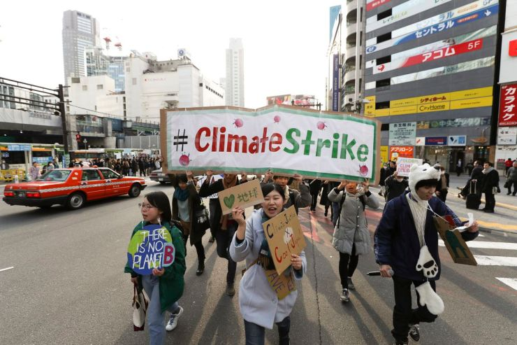Participants hold signs and shout slogans during the Fridays for Future march on March 15, 2019 in Tokyo, Japan.