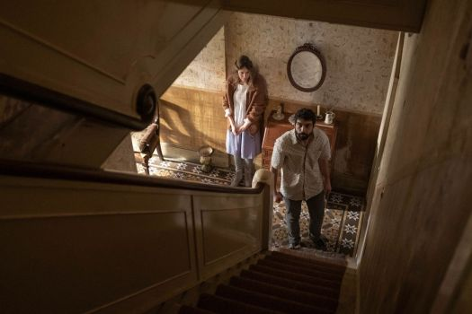Two people at the bottom of a staircase, looking up, in Romola Garai's horror movie Amulet.