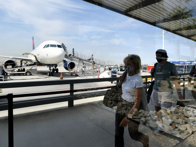 Air passengers walk on a sidewalk, and an airplane sits in the background.