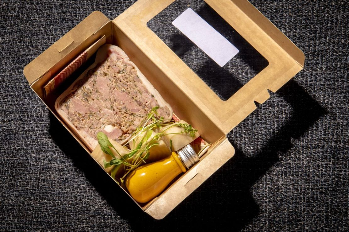 A terrine in a cardboard box with a bottle of orange sauce