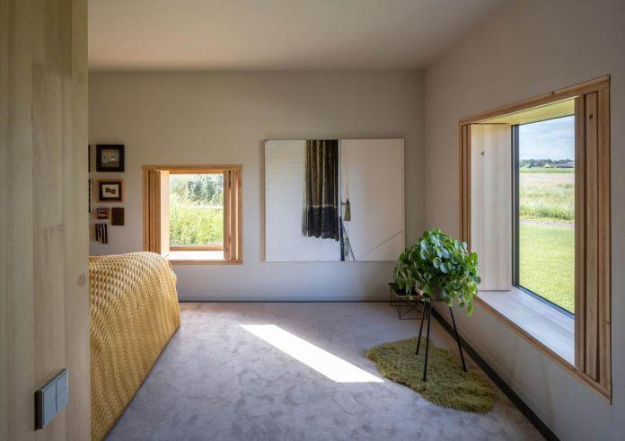 Спальня с квадратными окнами, серым ковром и легкой желтой кроватью за углом.