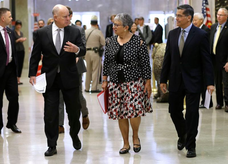 Gov. Jerry Brown, left, talks California Air Resources Board Chair Mary Nichols, and California Attorney General Xavier Becerra as they walk to a news conference to discuss a lawsuit filed by 17 states and the District of Columbia over the Trump administr