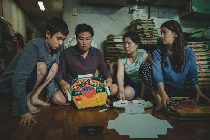 a korean son, dad, mother, and daughter sit in their tiny apartment folding pizza boxes in Parasite