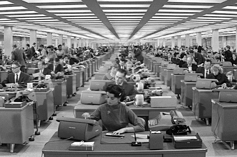 A 1960s-style open office, with rows of desks and people working.