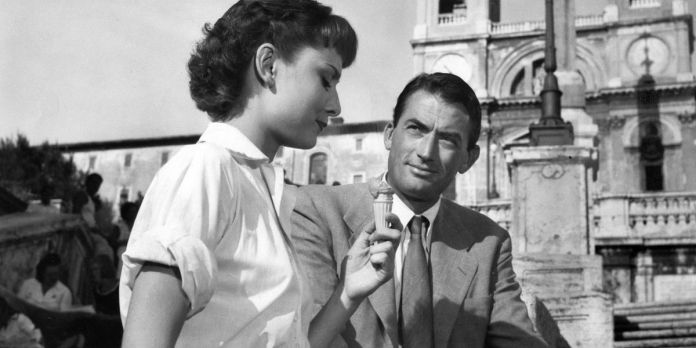 Audrey Hepburn eats an ice cream cone as Gregory Peck looks on in Roman Holiday