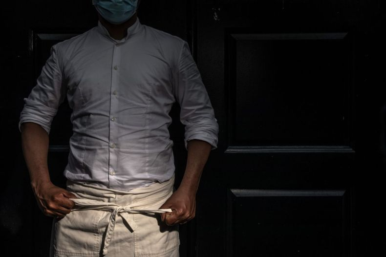 A service industry worker puts on an apron while wearing a face mask