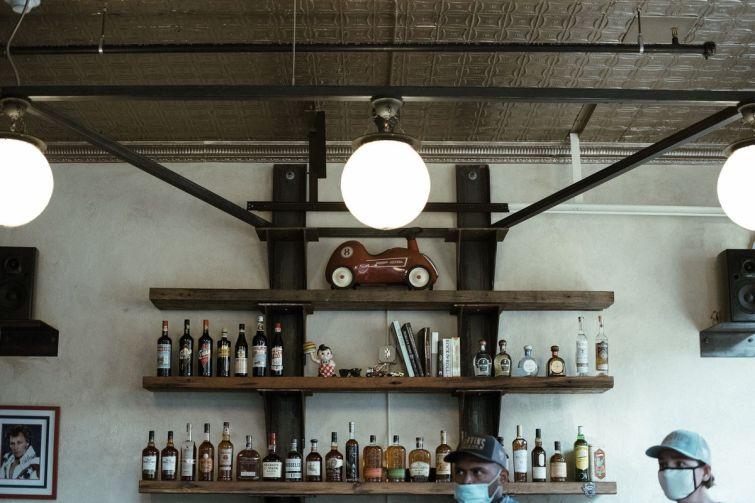 A set of three shelves holding liquor bottles and knick knacks behind a bar.