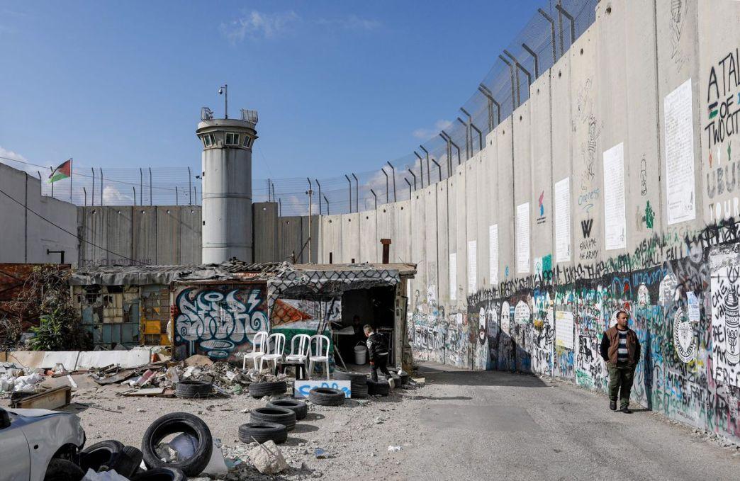 Un hombre camina junto a los murales de graffiti dibujados a lo largo de una sección de la controvertida barrera de separación de Israel en la ciudad de Belén en la Cisjordania ocupada el 7 de diciembre de 2019.