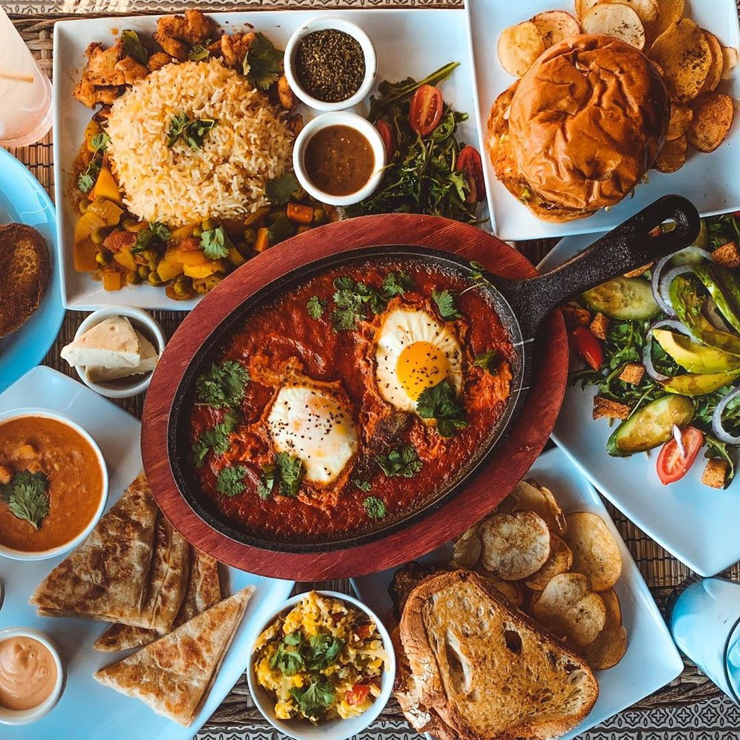 A spread of food from Yafa Cafe, including plates with rice, salad, and a cast-iron pan in the middle with eggs in red sauce.