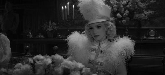 Gambar hitam putih Amanda Seyfried memerankan Marion Davies, dalam kostum yang terinspirasi sirkus dengan topi besar.