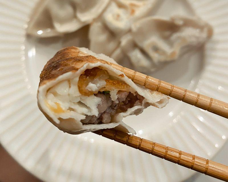 chopsticks hold a bitten-into dumpling.