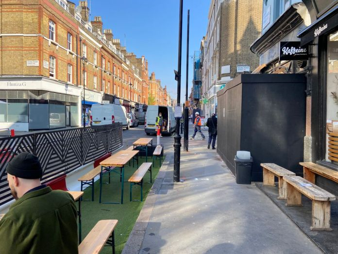 Tables and benches outside Kaffeine on the day al fresco dining (and resumption of drinks) under the blue skies of central London
