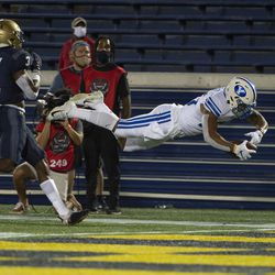 BYU running back Tyler Allgeier, right, dives for a touchdown as Navy cornerback Cameron Kinley (3) looks on during the first half of an NCAA college football game, Monday, Sept. 7, 2020, in Annapolis, Md.