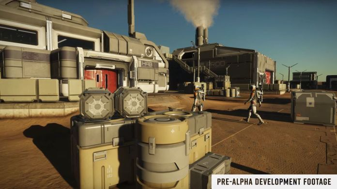 Two players walk amongst crates and boxes on a dusty planet. The sky is a pale blue, and they are wearing spacesuits.