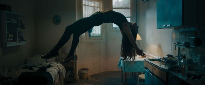 A woman floats on her back in mid-air in a dark room, back arched and long hair dangling