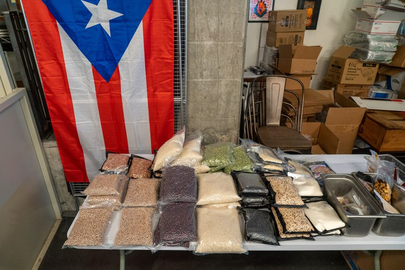 A puerto rican flag behind a table with packages of dried beans