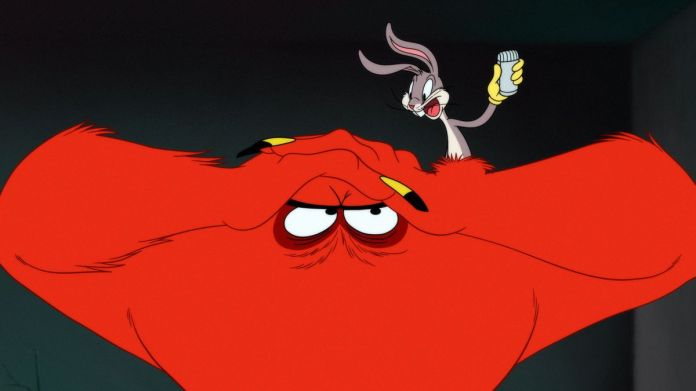 Bugs Bunny stands on the head of Gossamer, the big red monster from Looney Tunes cartoons.