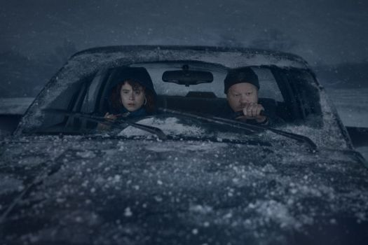 a couple sit in a car