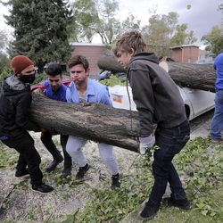 Michael Montoya, Jorge Guzman and Eric Starkey and Isaac Perry move a piece of a tree that fell on Perry's car during a windstorm in Salt Lake City on Tuesday, Sept. 8, 2020.