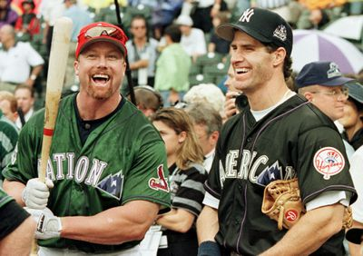 Mark McGwire (L) of the St. Louis Cardinals laughs
