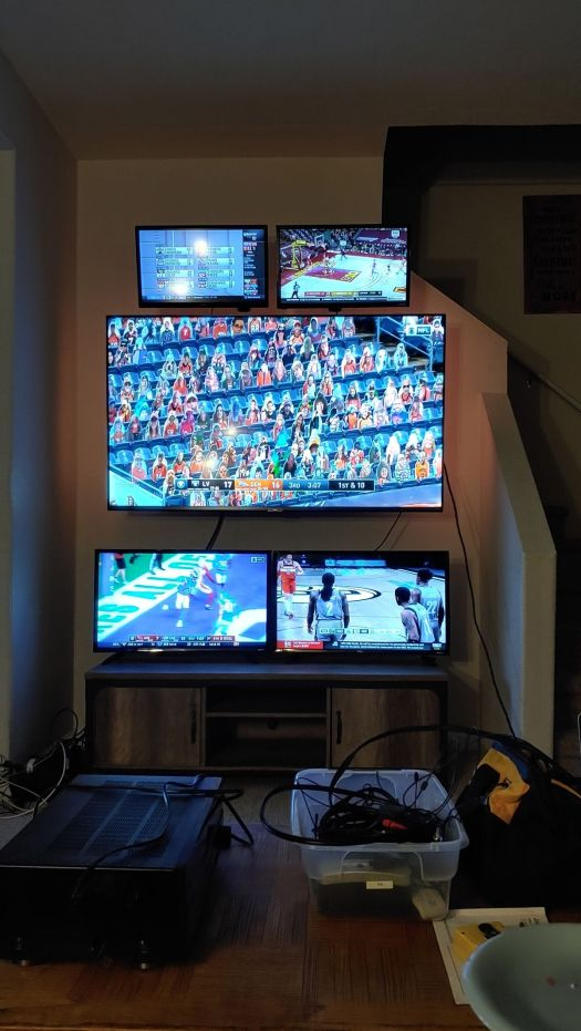 a photo of one large TV with four smaller TVs mounted around it — two above and two below — in a living room