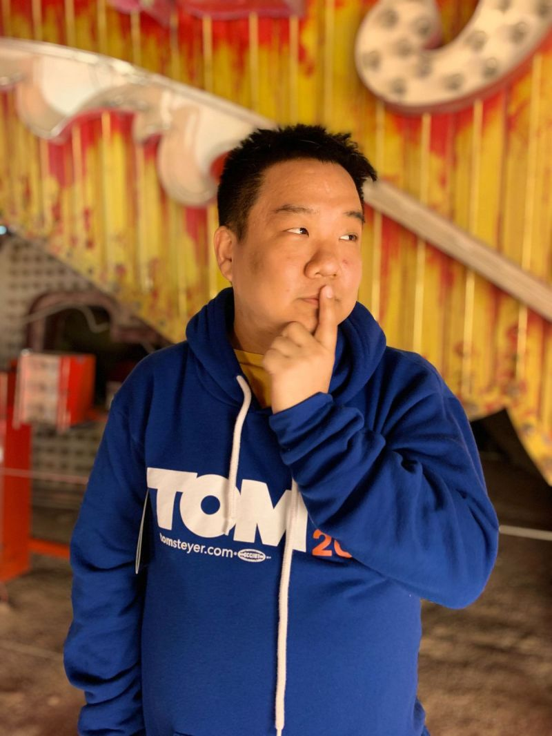 Tony Choi poses in a Tom Steyer 2020 sweatshirt.