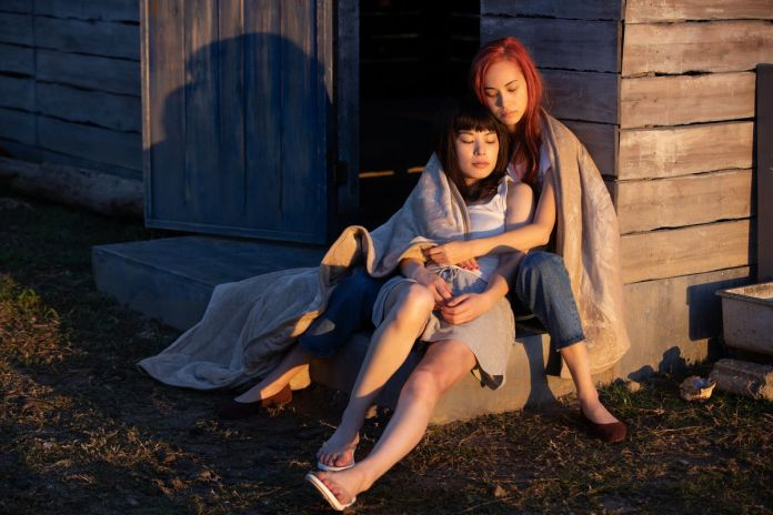 Kiko Mizuhara and Honami Satô cuddle in front of a cabin in Ride or Die