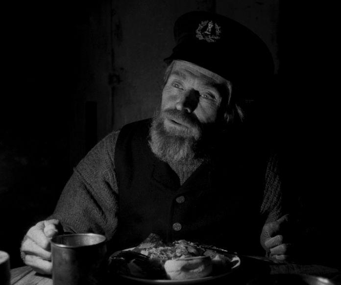 Thomas (Dafoe) parle devant une assiette de nourriture et une tasse.