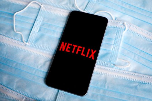 A cellphone showing the Netflix logo rests atop multiple disposable face masks.