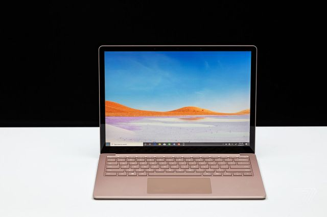 A gold Microsoft Surface Laptop 3 on a white table in front of a black background