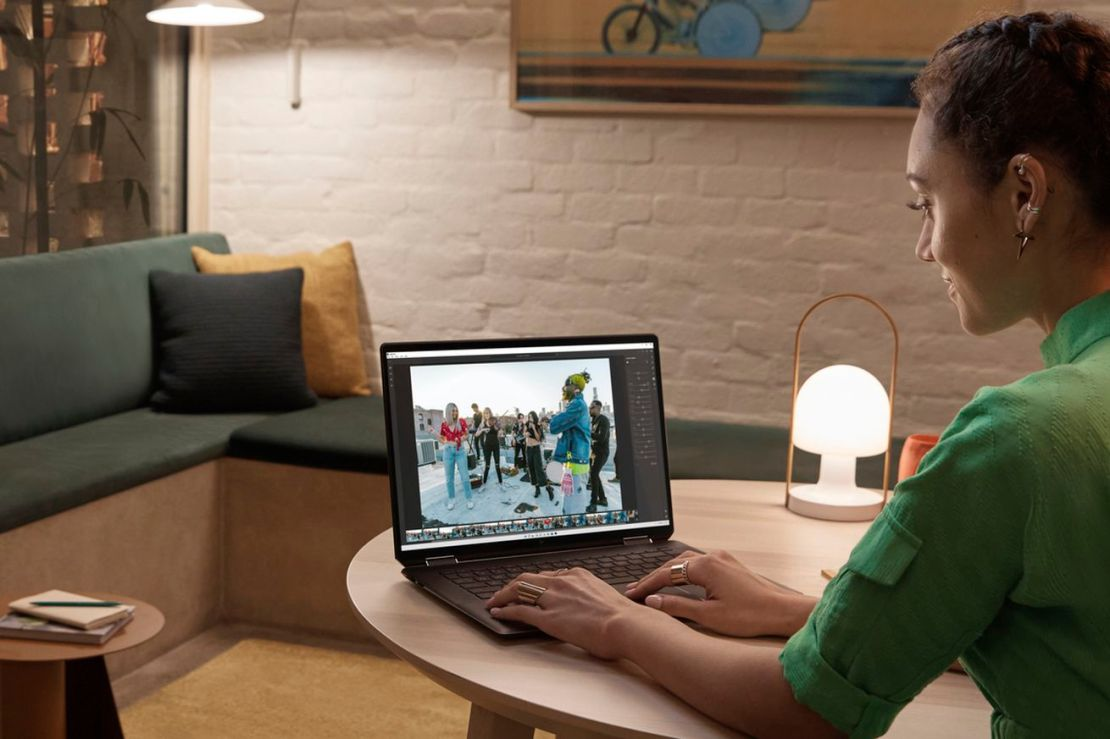 A user in a red dress types on the HP Spectre x360 16 in an evening room at a small wooden table. The screen displays a photo of a group of urban dancers in an outdoor scene in an editing program. To its left is a small lit lamp.
