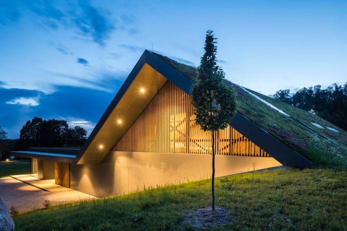 Дом имеет секцию со скатной зеленой крышей.