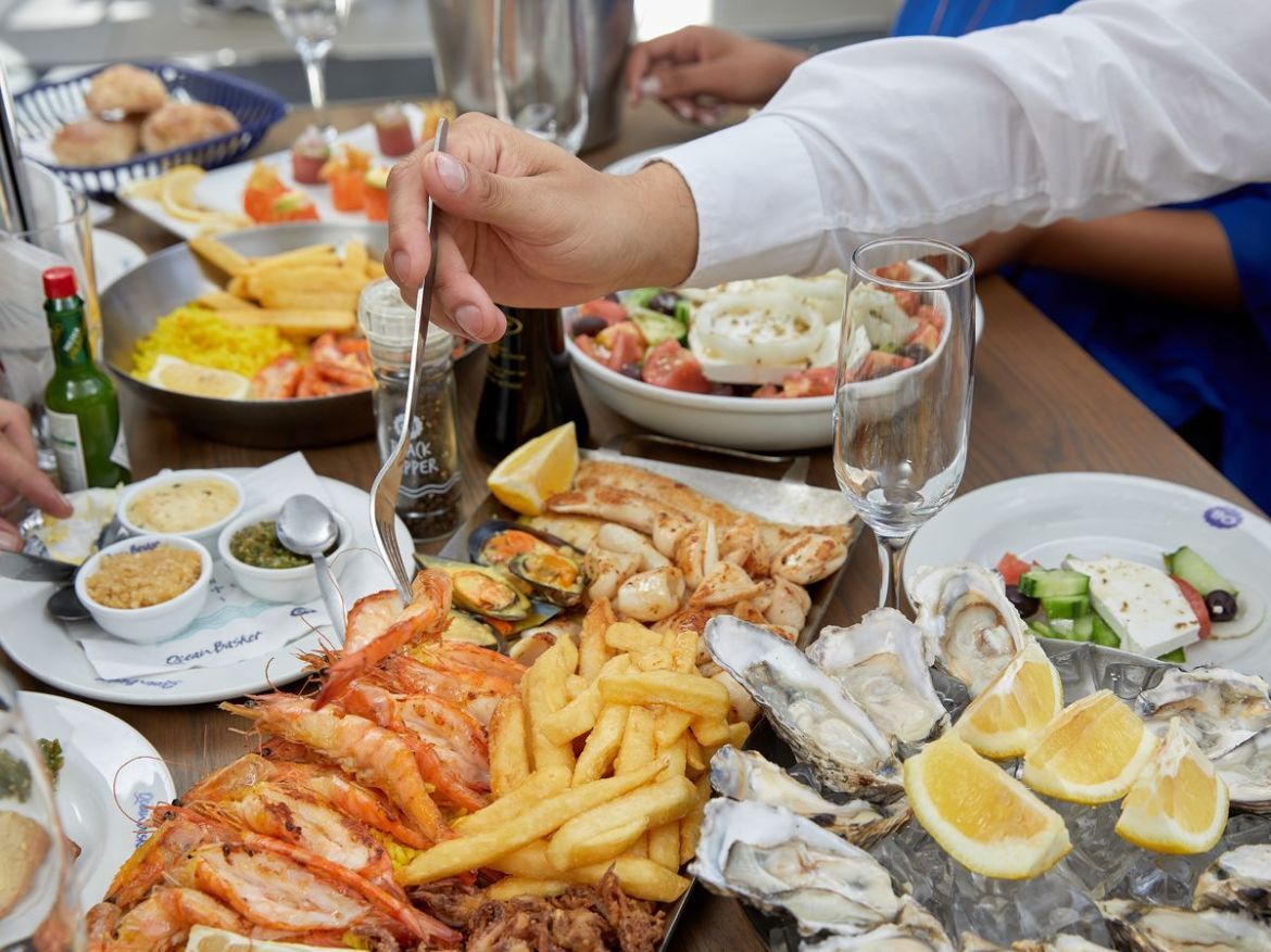 A hand reaches across a table with a fork to take an item from a large platter of various seafood, on a table filled with other dishes including a tray of oysters, fried seafood with French fries, Greek salad, and glasses for wine
