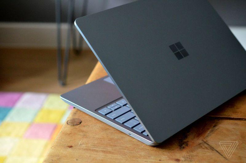 Il Surface Laptop Go all'angolo di un tavolo semiaperto, visto dal retro.