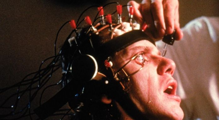 Malcolm McDowell is seen in closeup with a metal apparatus strapped to his head and his eyes held open with clamps as a doctor drips fluid into his eyes in A Clockwork Orange.