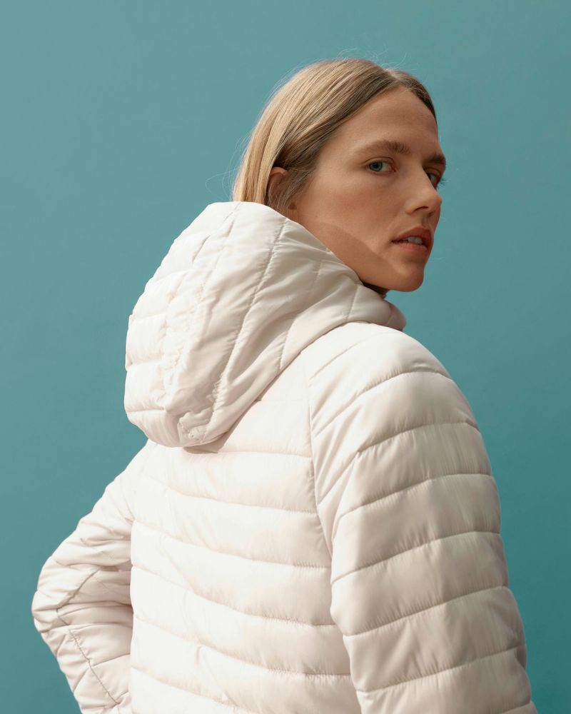 A model wears a white Everlane puffer jacket.