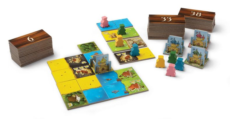 A game of Kingdomino laid out on the table, its many numbered tiles ordered randomly in stacks.