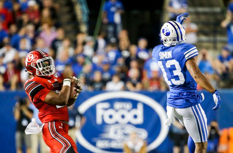 Utah Utes defensive back Julian Blackmon (23) makes an interception on a pass intended for BYU wide receiver Micah Simon (13) during the second half of the Utah-BYU football game at LaVell Edwards Stadium in Provo on Thursday, Aug. 29, 2019. Blackmon returned the pick for a touchdown.