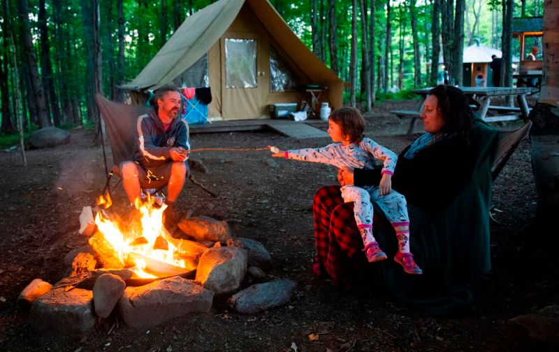 A family around a campfire with a tent
