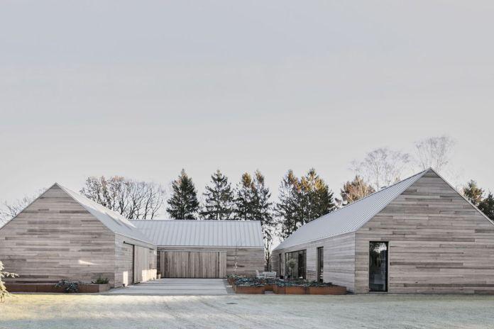 Три бледных кедровых габитовых дома окружают внутренний двор. Деревья выстраиваются на заднем плане.