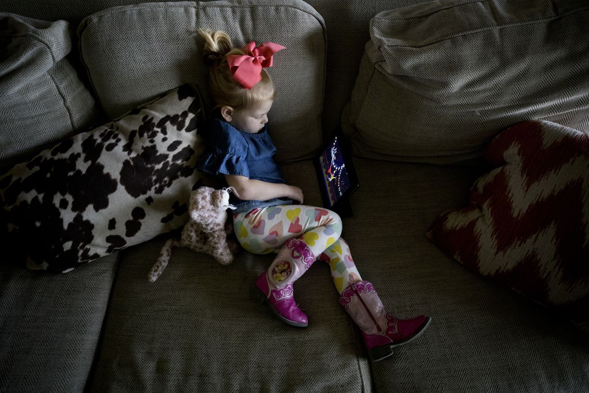 Lily Clark, 3, watches a movie in her home.