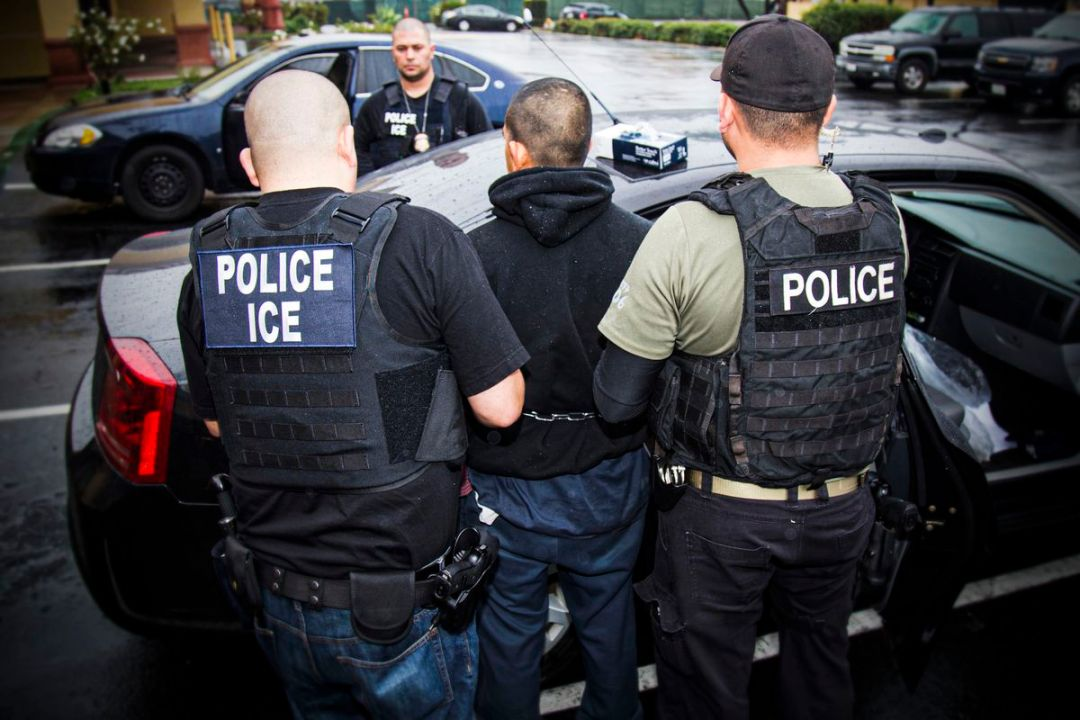 ICE agents conduct an arrest.