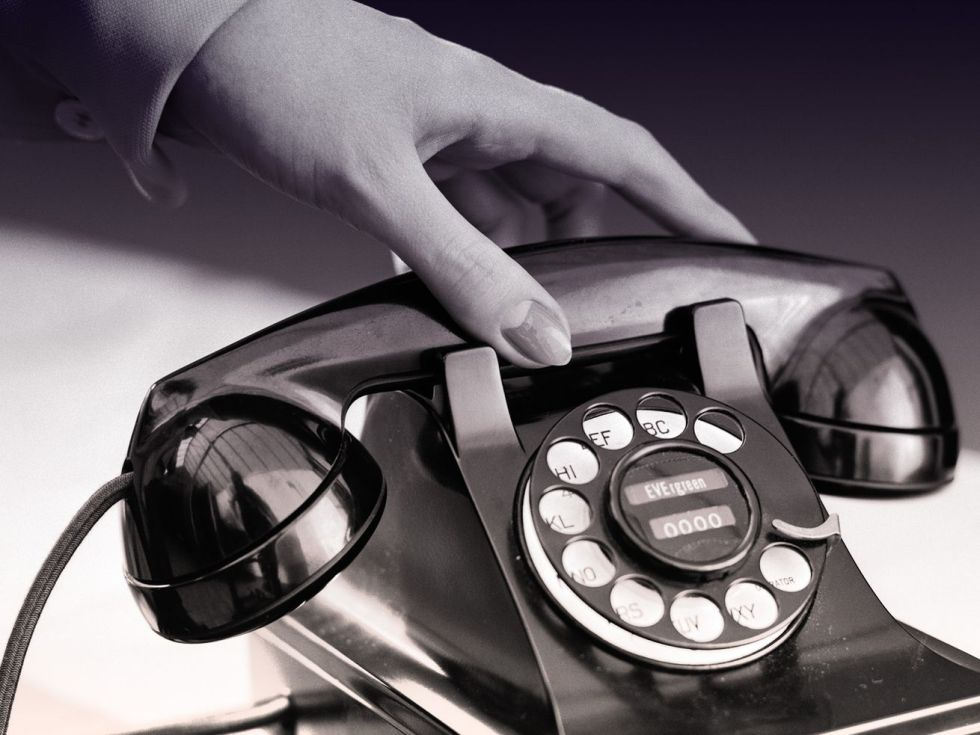 Black-and-white photo of a hand picking up a telephone receiver on a retro rotary phone.