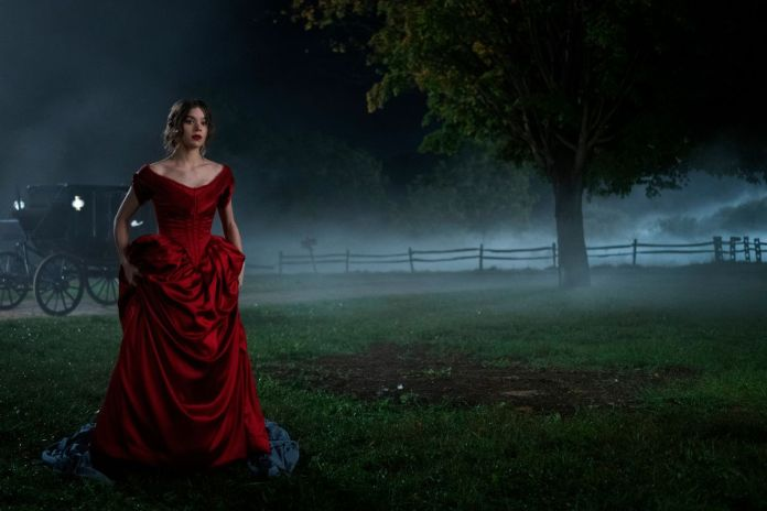 A young Emily Dickinson (Hailee Steinfeld) wears a red party dress walking through a dark, hazy field in a promotional image from the Apple TV Plus show, Dickinson
